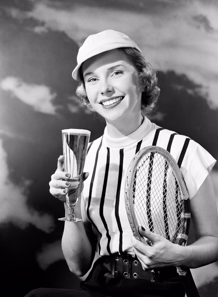 Portrait of smiling woman holding champagne and tennis racket : Stock Photo