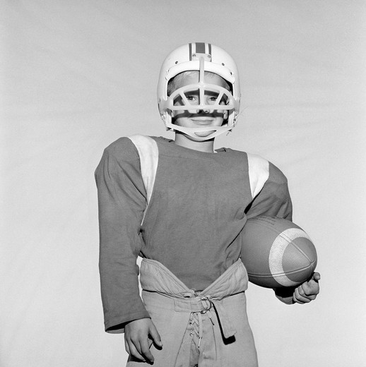 Stock Photo: 255-418594 Boy wearing football helmet and holding football