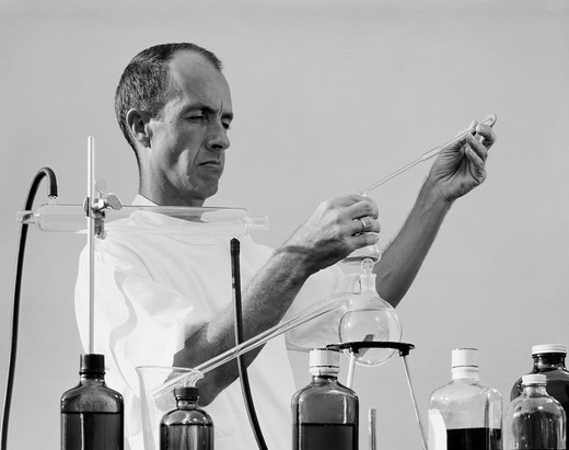 Scientist mixing chemicals in laboratory : Stock Photo