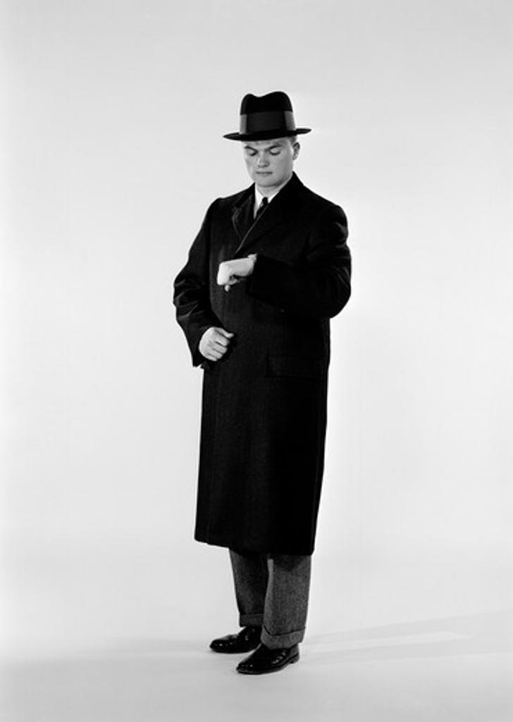 Stock Photo: 255-419001 Studio shot of man in coat looking at wristwatch