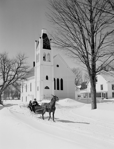 People on sleigh, church in the background : Stock Photo