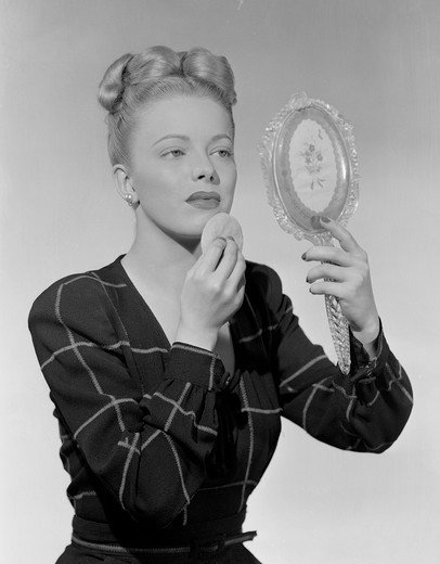 Stock Photo: 255-419711 Portrait of woman looking at mirror and using powder puff