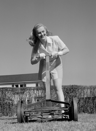 Stock Photo: 255-419773 Woman mowing lawn