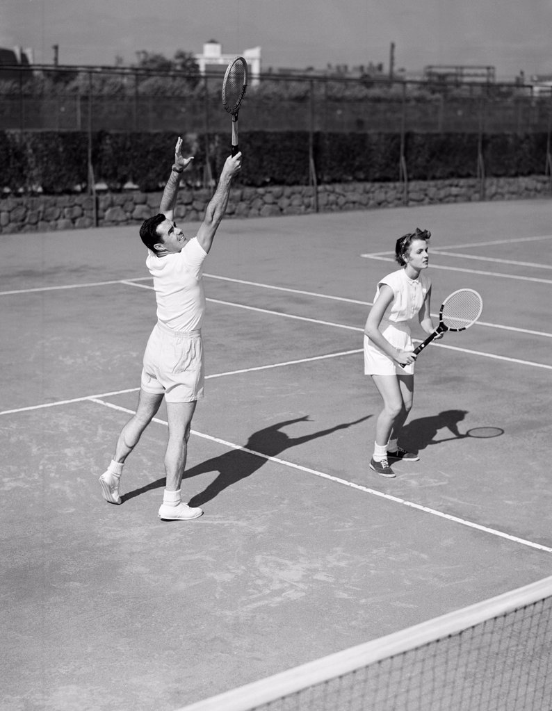 Stock Photo: 255-420299 Young couple playing doubles tennis