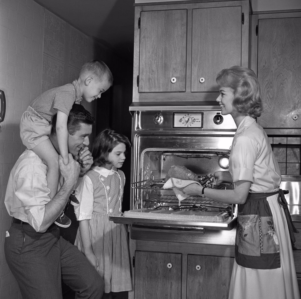 Mother showing freshly baked chicken to husband and children : Stock Photo