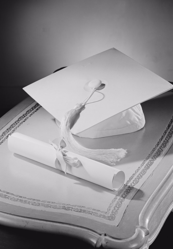 Stock Photo: 255-421411C Graduation diploma and mortar board on bedside table