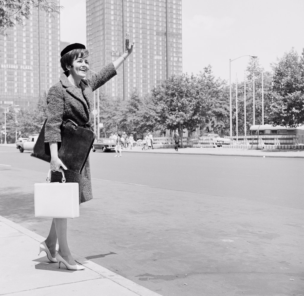 Stock Photo: 255-421936 Elegant woman on street waving for taxi