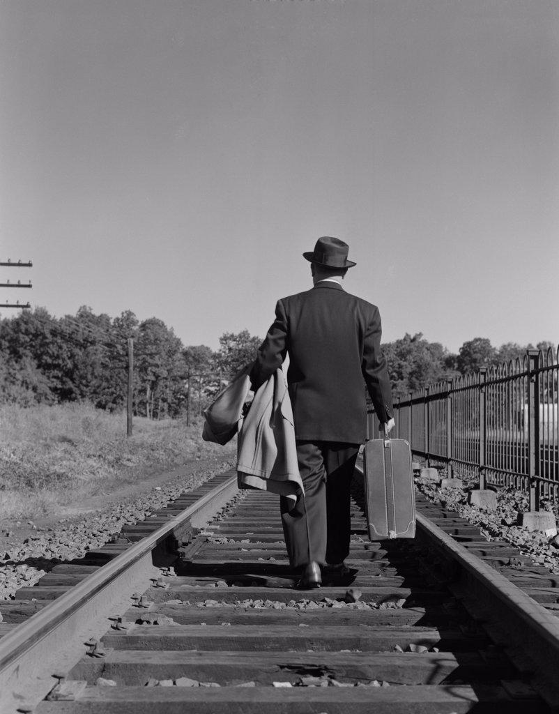 Businessman walking down railway tracks : Stock Photo