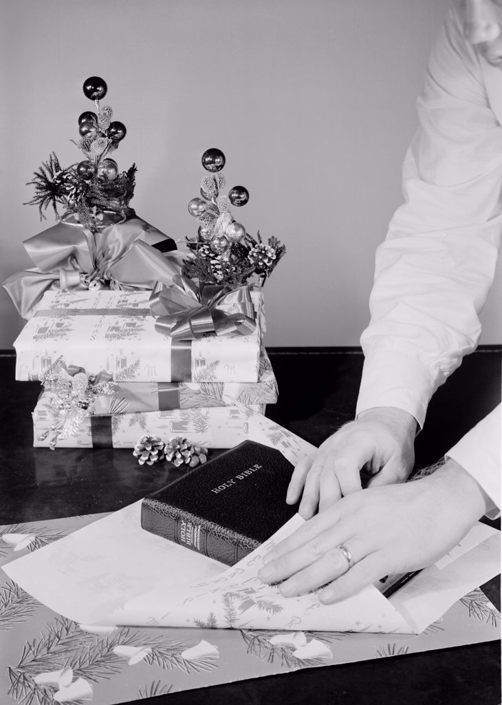 Stock Photo: 255-422258 Man wrapping bible as Christmas gift