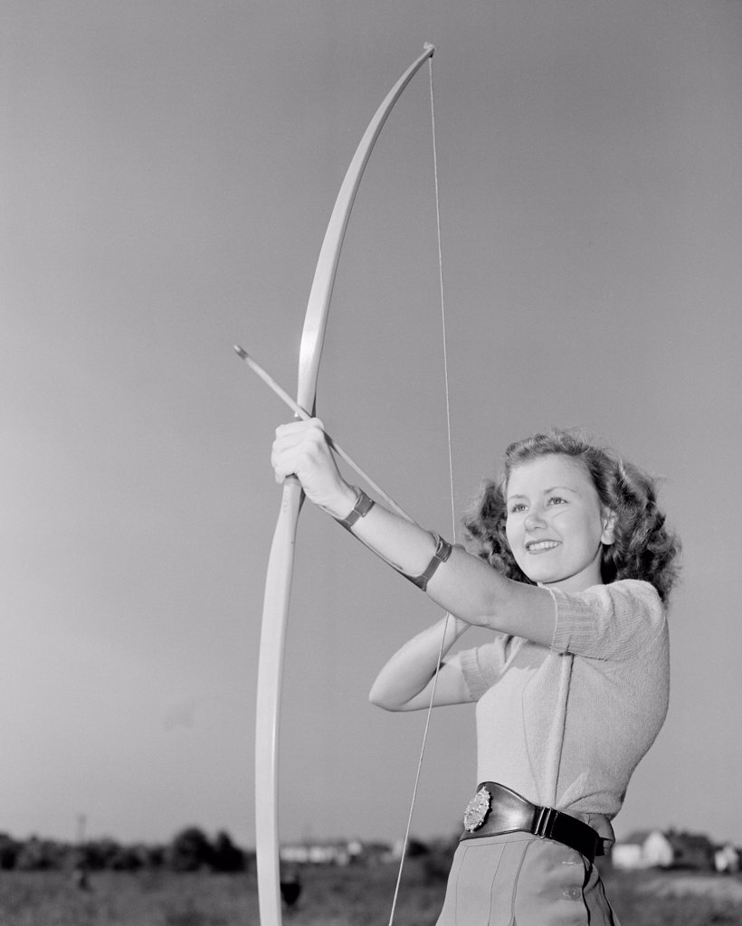 Stock Photo: 255-422355 Young woman shooting with bow