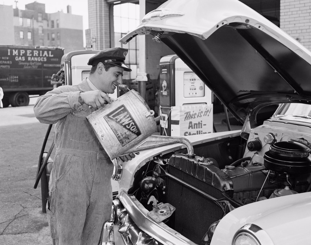 Stock Photo: 255-422438 Mechanic pouring oil into car engine