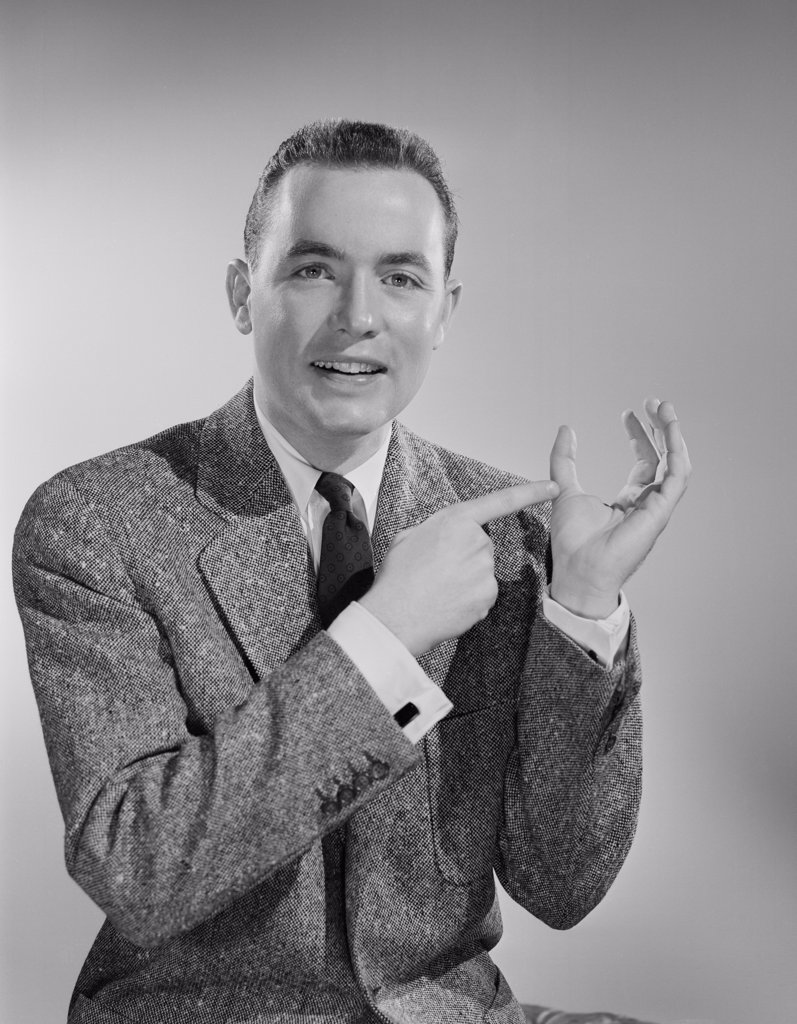 Studio portrait of mid adult man showing thumb : Stock Photo