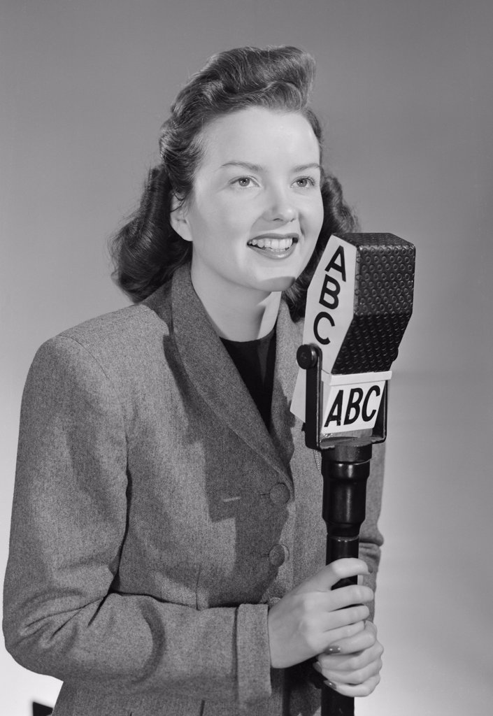 Stock Photo: 255-422893 Studio portrait of female reporter speaking into microphone