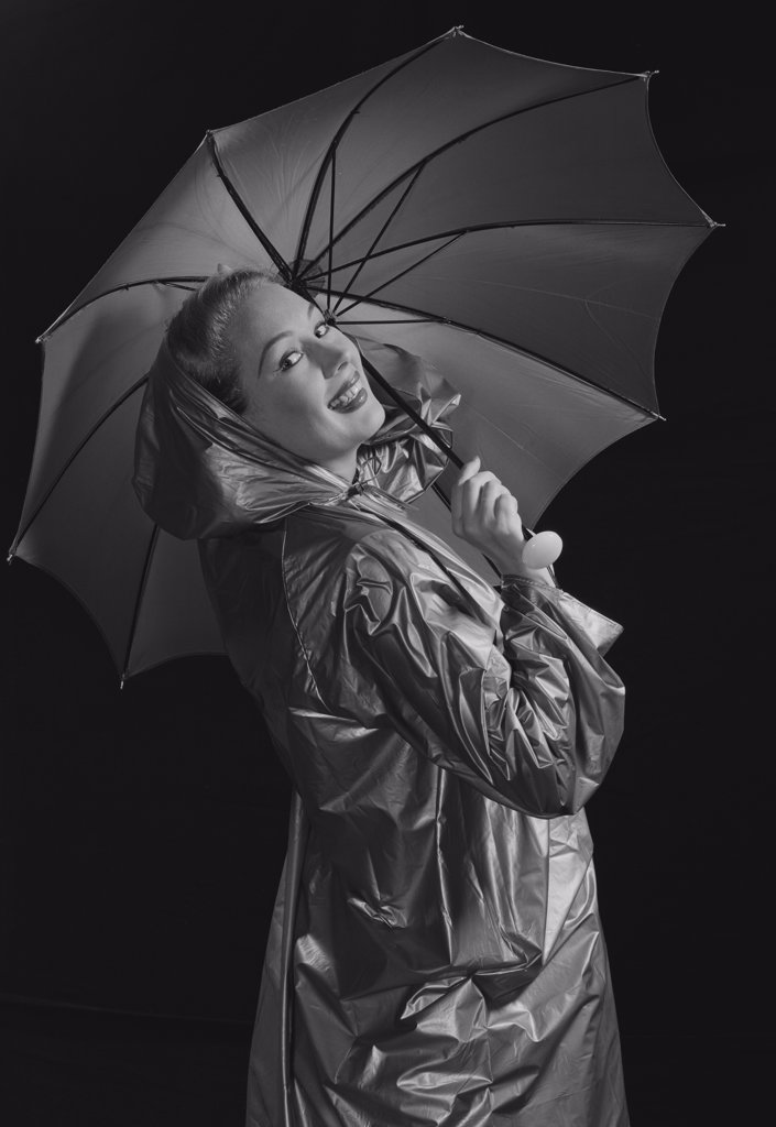 Stock Photo: 255-422906A Young woman holding umbrella and wearing raincoat