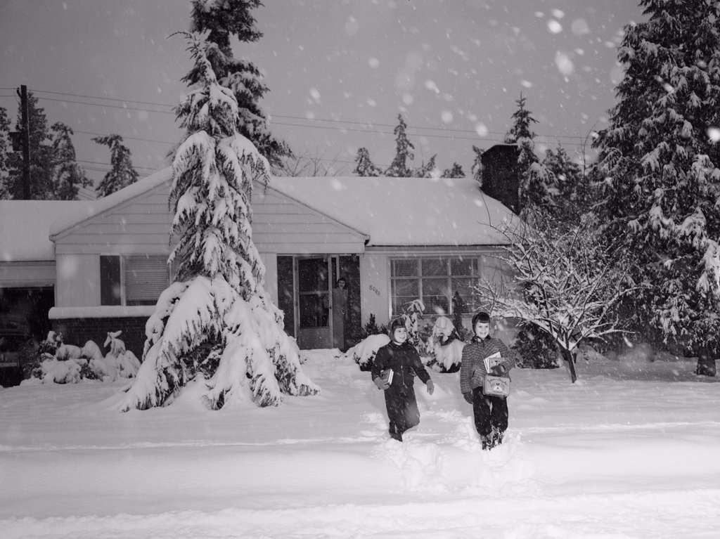 Kids leaving  home during heavy snow fall : Stock Photo