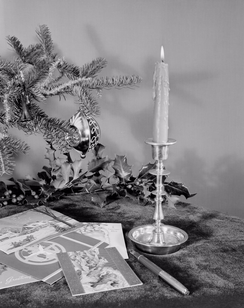 Stock Photo: 255-424090 Christmas cards, candle, holly and Christmas tree branch