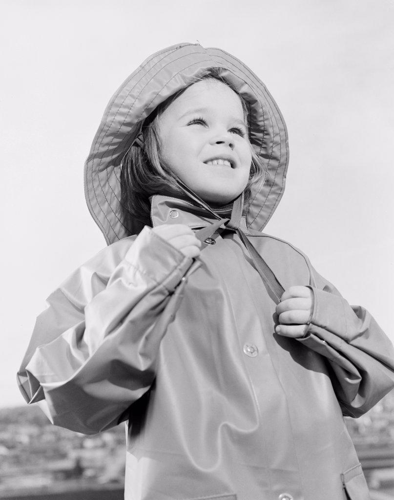 Girl wearing raincoat and rain hat : Stock Photo