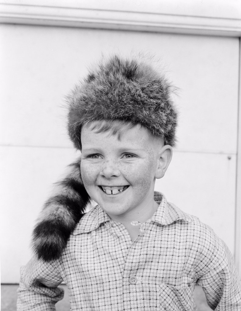 Boy wearing coonskin cap smiling : Stock Photo