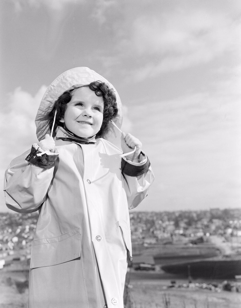Stock Photo: 255-424550 Girl wearing raincoat looking away and smiling