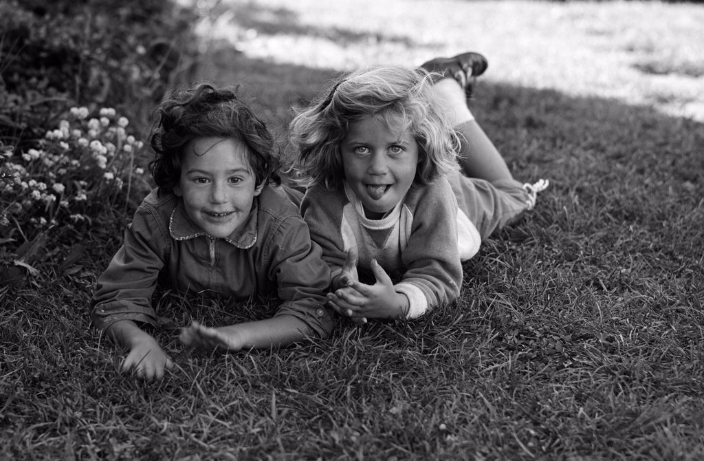 Stock Photo: 255-424565 Portrait of two girls lying on lawn