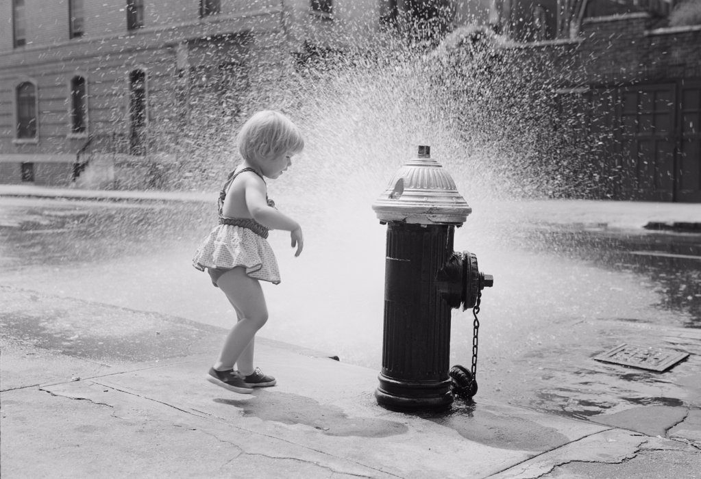 Little girl cooling off at fire hydrant on street : Stock Photo