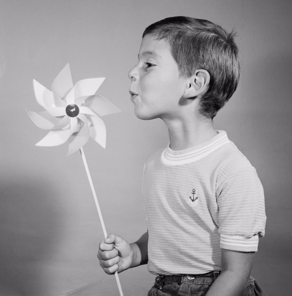 Studio shot of boy blowing at pinwheel : Stock Photo