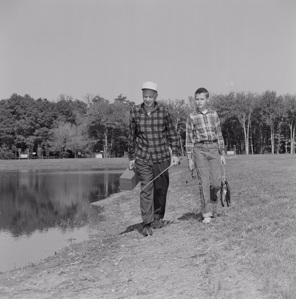 Stock Photo: 255-424808 USA, Father and son with fish and fishing equipment
