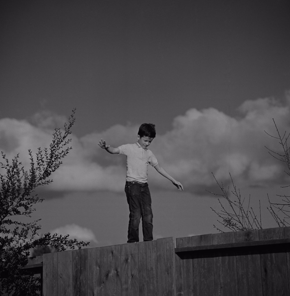 Stock Photo: 255-424915 Boy balancing on fence