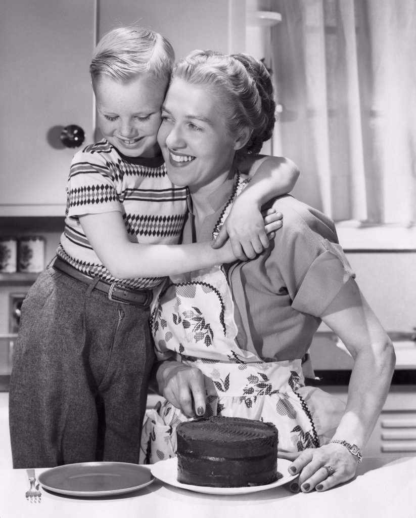 Stock Photo: 255-42766B Boy hugging his mother and smiling in front of cake on table