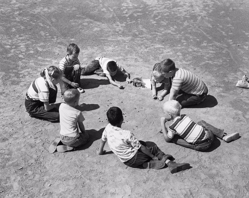 High angle view of a group of children playing with marbles : Stock Photo