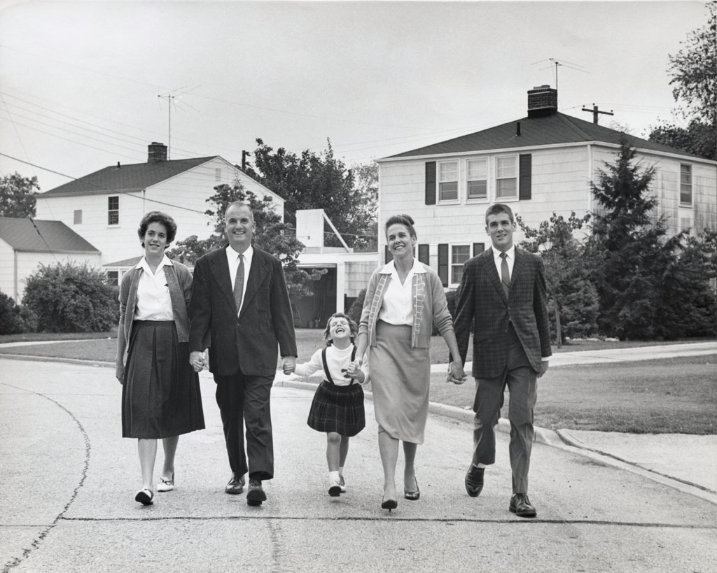 Stock Photo: 255-4385 Granddaughter walking with parents and grandparents on suburban road