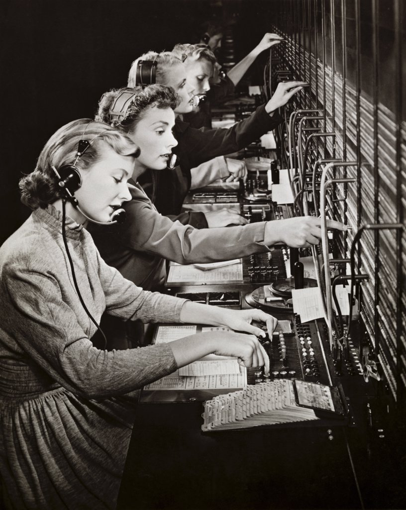 Stock Photo: 255-4644 Side profile of a group of telephone operators operating switchboards