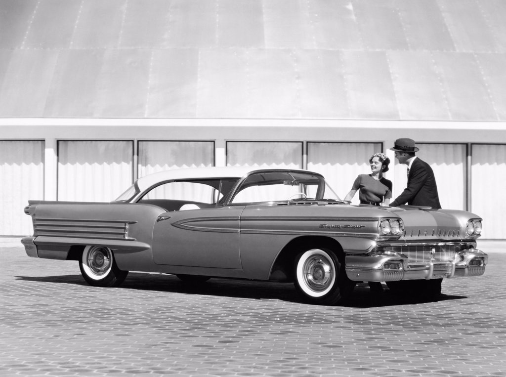 Man and woman standing behind a 1958 Oldsmobile Dynamic 88 Holiday Coupe : Stock Photo