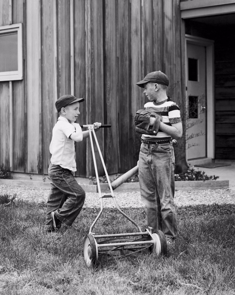 Stock Photo: 255-47957 Boy mowing the lawn with a lawn mower and his friend talking to him
