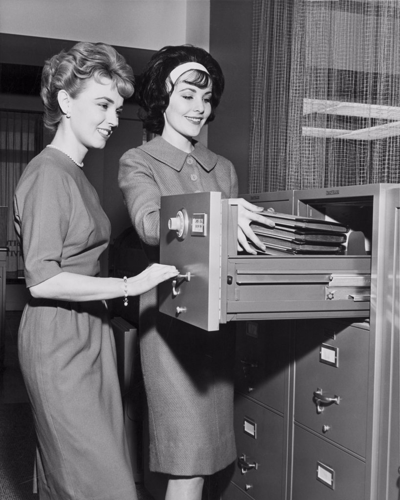 Two female office workers arranging files in filing cabinet : Stock Photo