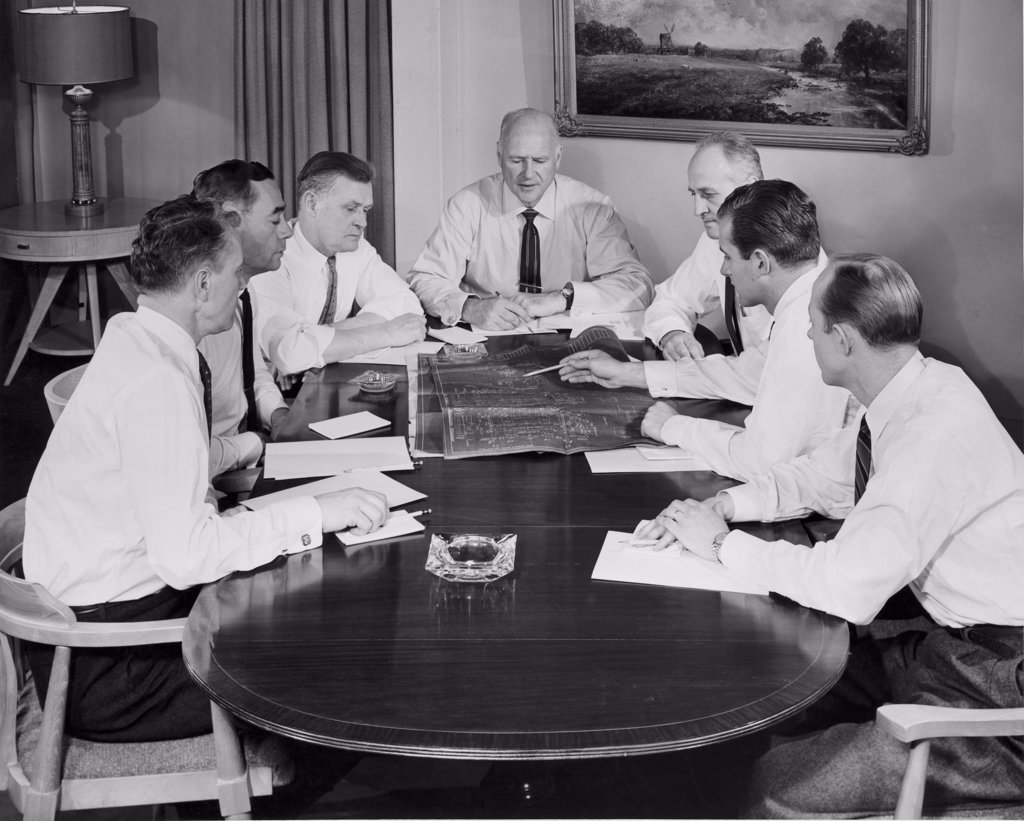 Stock Photo: 255-48690 Business executives looking at blueprint in conference room