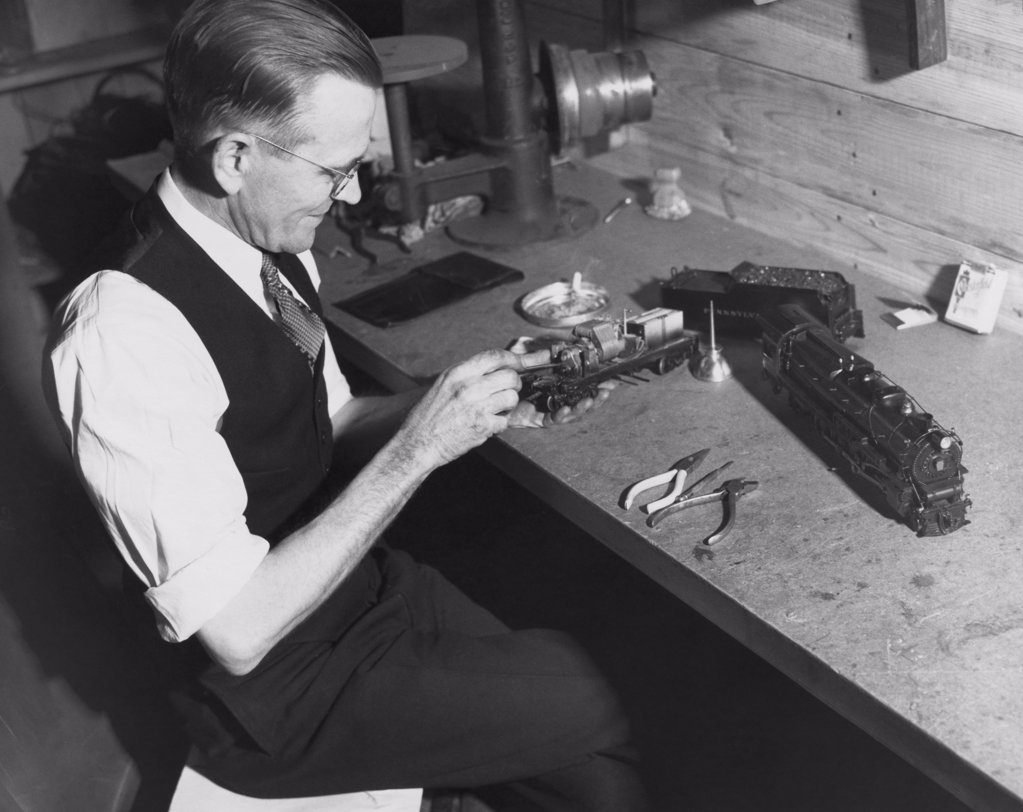 Senior man making a miniature train : Stock Photo