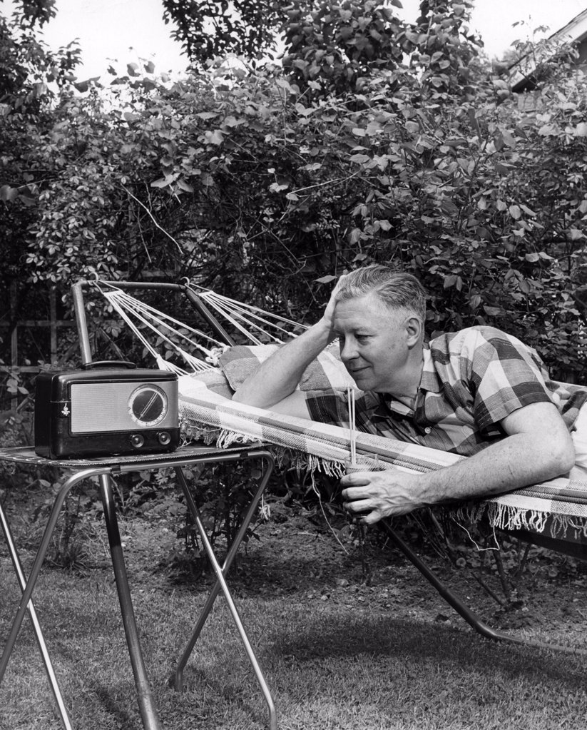 Stock Photo: 255-49046 Man relaxing in hammock listening to radio