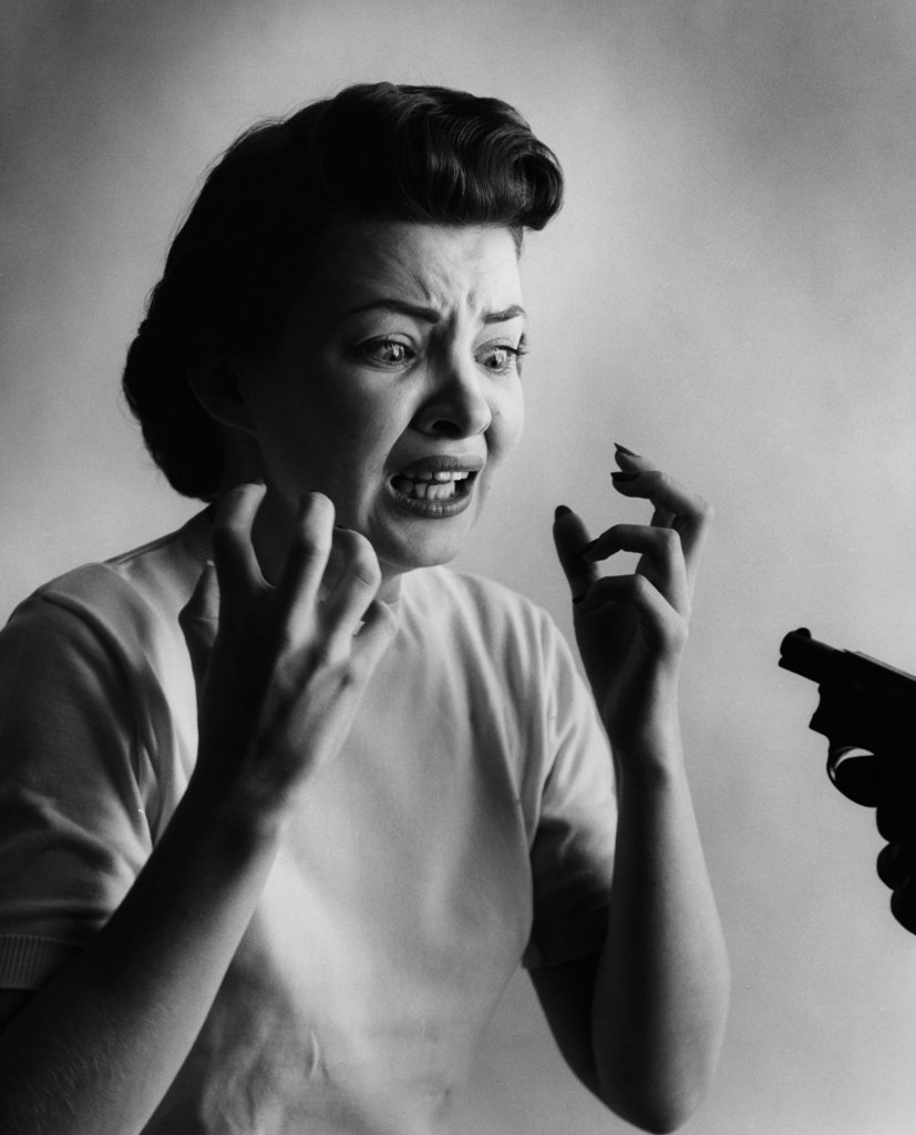 Stock Photo: 255-49629 Studio shot of woman being threatened with gun