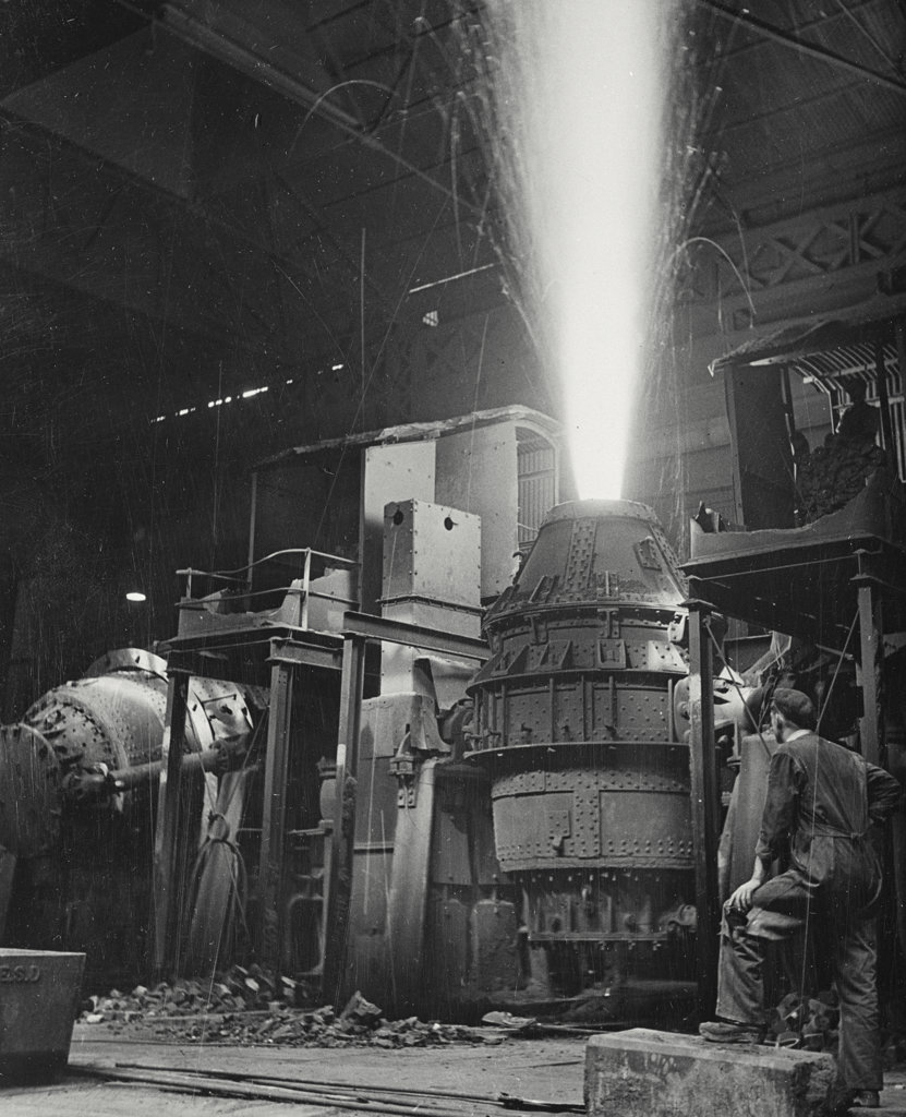 Stock Photo: 255-5492 Rear view of a mature man looking at a Bessemer converter in a steel mill