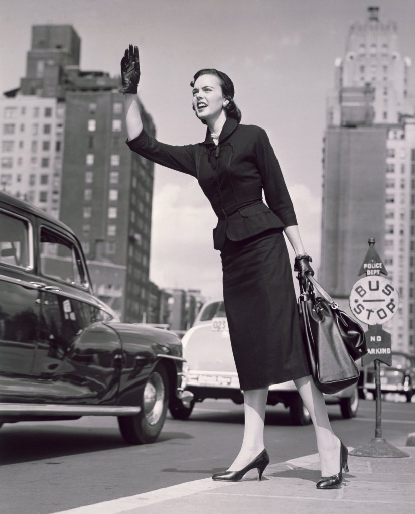 Stock Photo: 255-5621 Low angle view of a young woman hailing a taxi