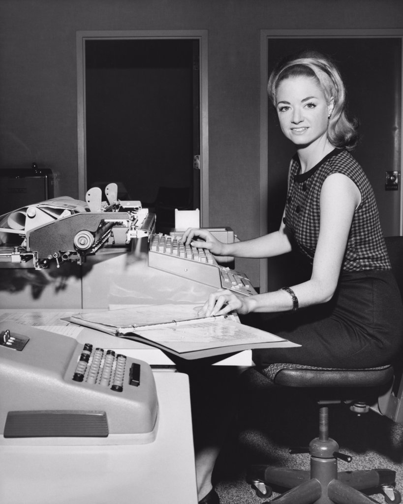 Businesswoman typing on a typewriter in an office : Stock Photo