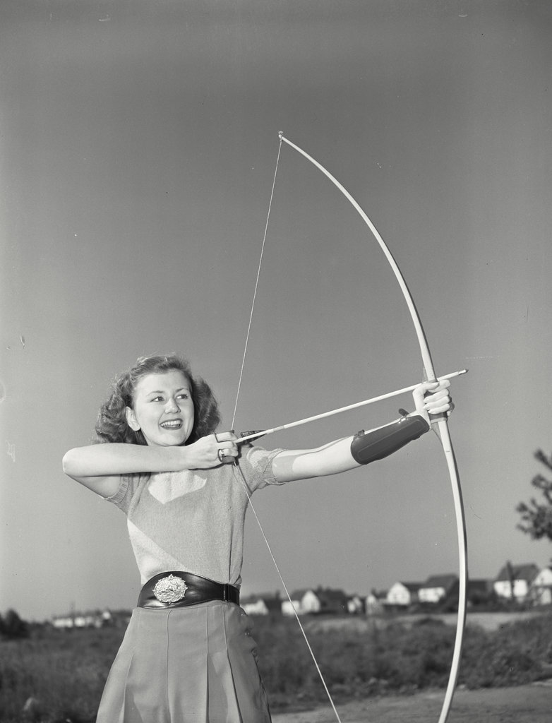 Young woman aiming bow : Stock Photo