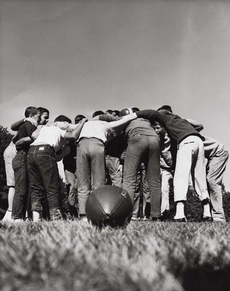 Rear view of football players in a huddle : Stock Photo