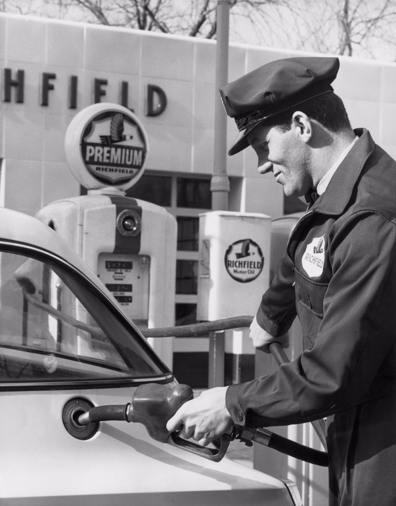 Stock Photo: 255-6642 Side profile of a gas station attendant filling up a car