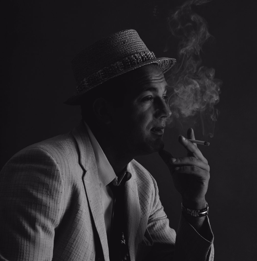 Studio portrait of man wearing hat, smoking cigarette : Stock Photo