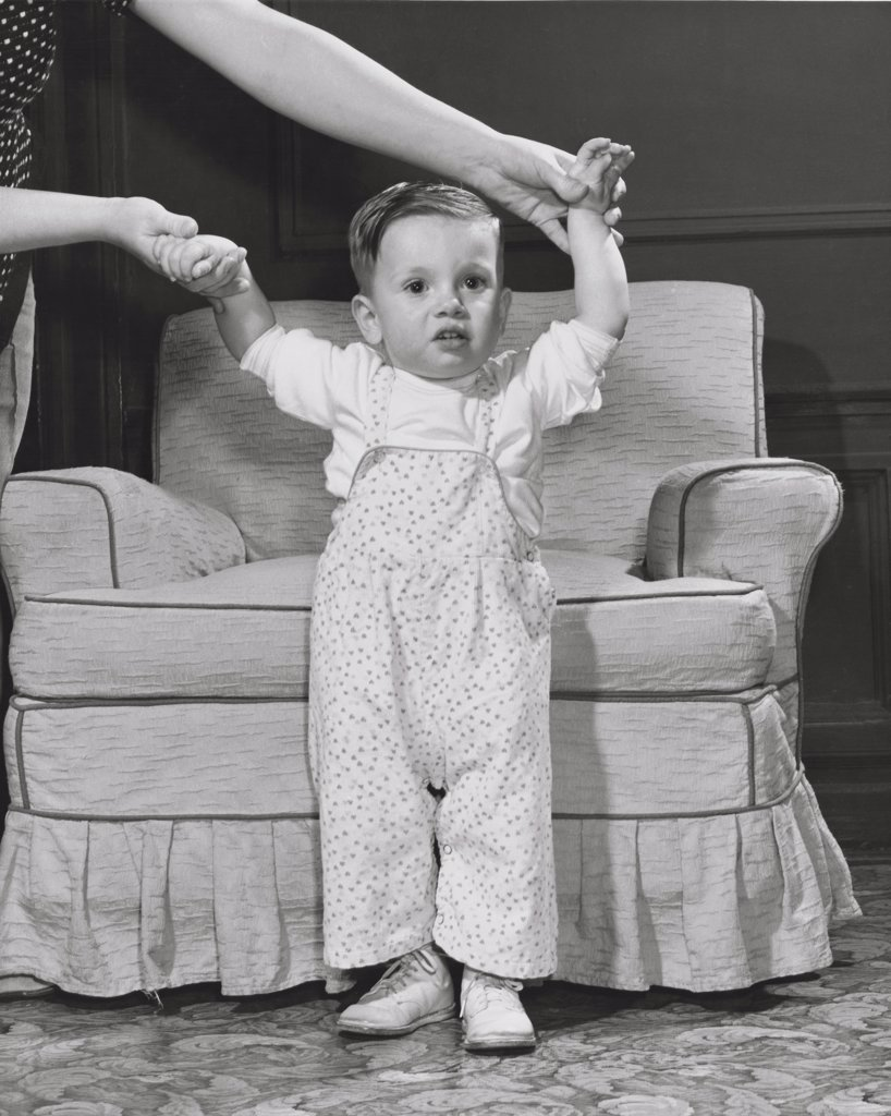 Stock Photo: 255-7569 Baby girl standing in front of an armchair