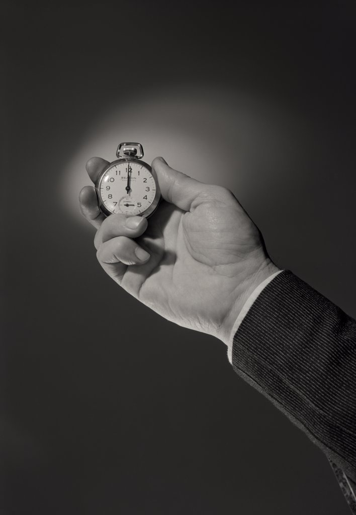 Businessman holding pocket watch : Stock Photo