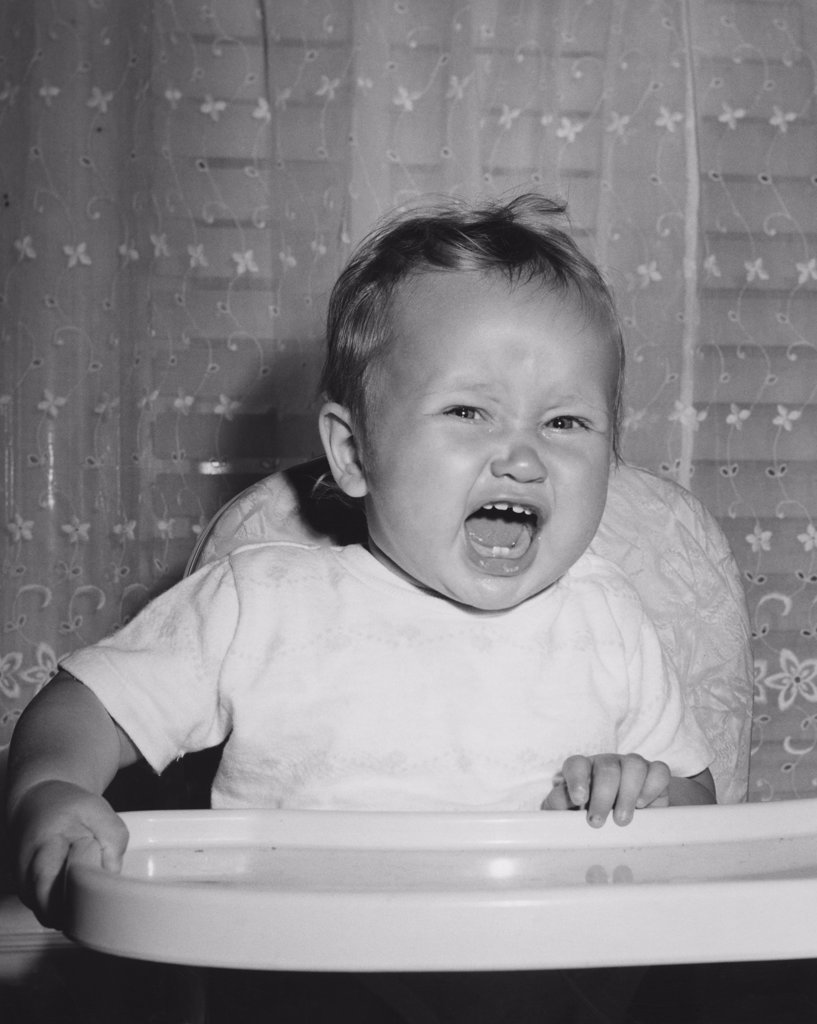 Stock Photo: 255-9719 Close-up of a baby sitting in a high chair and crying