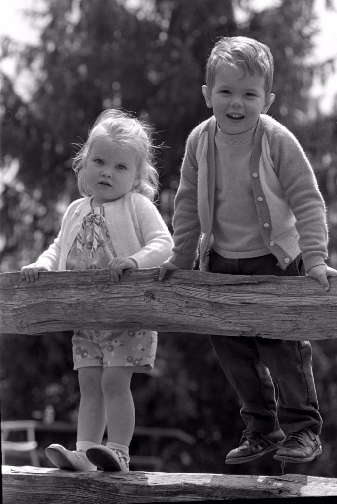 Stock Photo: 255-9984 Boy and girl standing on rail fence